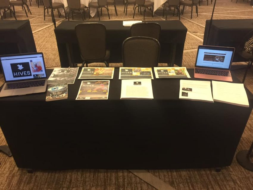 Image shows a table stacked with access copies of handouts (large and small print) and two laptops showing HIVES promotional materials.